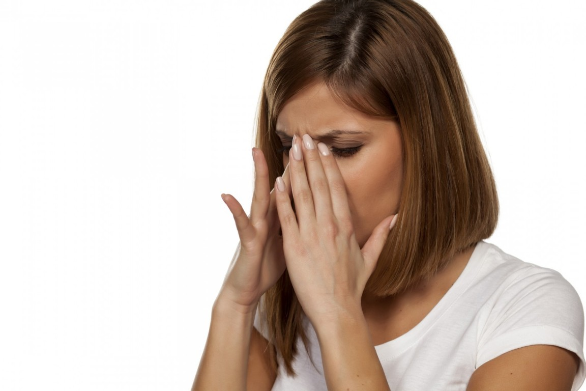 young beautiful woman has pain in the sinuses